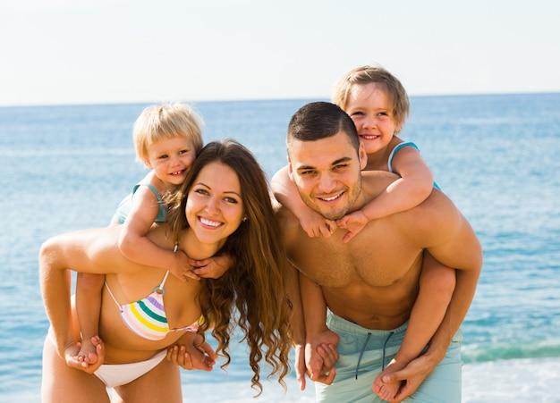 Familie van vier op het strand Gratis Foto
