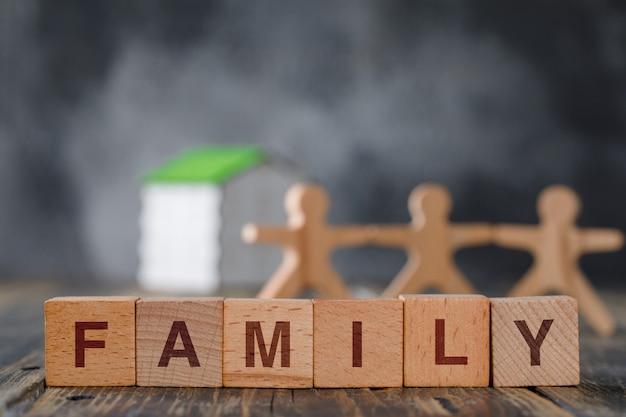 Familie veiligheidsconcept met houten figuren van mensen, kubussen, model huis zijaanzicht. Gratis Foto