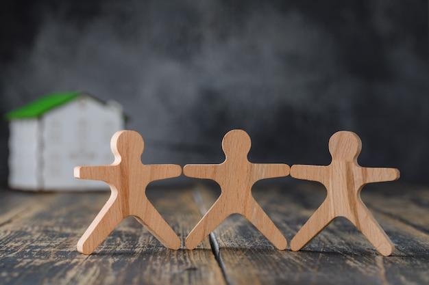 Familie veiligheidsconcept met houten figuren van mensen, model huis zijaanzicht. Gratis Foto