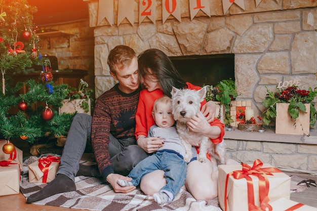 Familie zit in de voorkant van de open haard met hun baby en hun hond en een kerstboom Gratis Foto