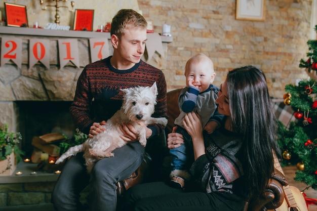 Familie zitten in een enkele fauteuil met haar hond en haar baby Gratis Foto