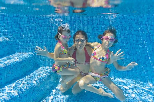 Familie zwemmen in zwembad onderwater Premium Foto