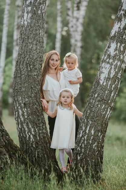 Familiefoto-moeder met dochters in het park. foto van jonge moeder met twee schattige kinderen buiten in het voorjaar, mooie vrouw met dochter plezier Premium Foto