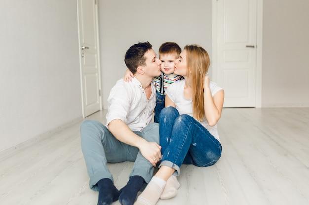 Familiefoto van twee jonge ouders die met hun jongenskind spelen Gratis Foto
