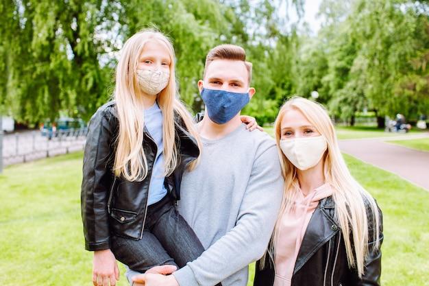 Familieleden die elkaar omhelzen, glimlachend in de camera met stoffen gezichtsmaskers op. Premium Foto