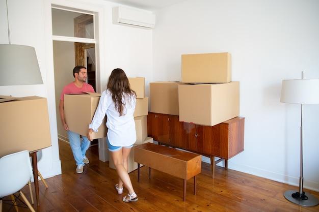 Familiepaar verlaat hun appartement met kartonnen dozen en meubels Gratis Foto