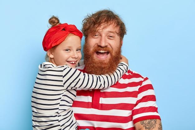 Familieportret van gelukkige dochter draagt rode hoofdband en gestreepte trui, omhelst opgetogen vader met dikke gemberbaard en krullend haar, hou heel veel van elkaar Gratis Foto
