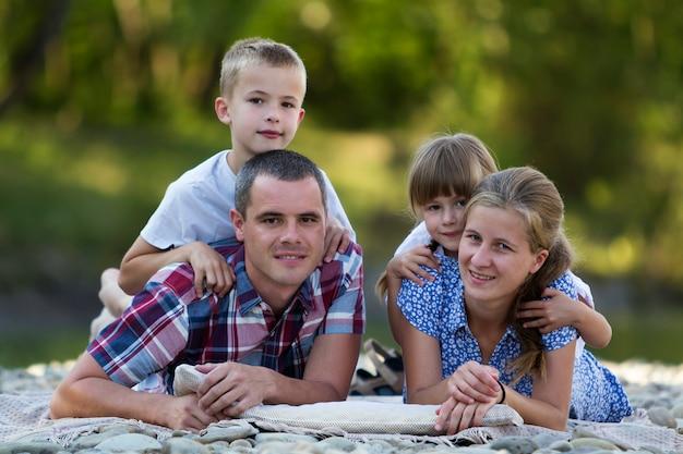 Familieportret van jonge gelukkige moeder, vader en twee schattige blonde kinderen, jongen en meisje op heldere zomerdag met groen. gelukkig familierelaties, liefde, zorg en perfecte vakantie concept Premium Foto