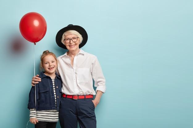 Familieportret van kleindochter en oma omhelzen en vieren vakantie, houden luchtballon vast, dragen feestelijke kleding, drukken positieve emoties uit die op blauwe muur worden geïsoleerd. generatie en fest concept Gratis Foto