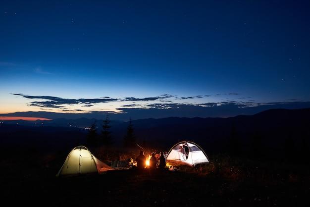 Familiewandelaars die een rust hebben bij nacht die in bergen kamperen Premium Foto