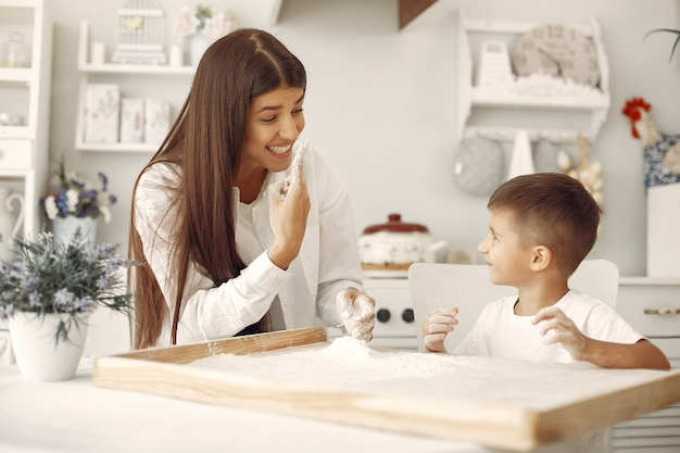 Familiezitting in een keuken en kook het deeg voor koekjes Gratis Foto