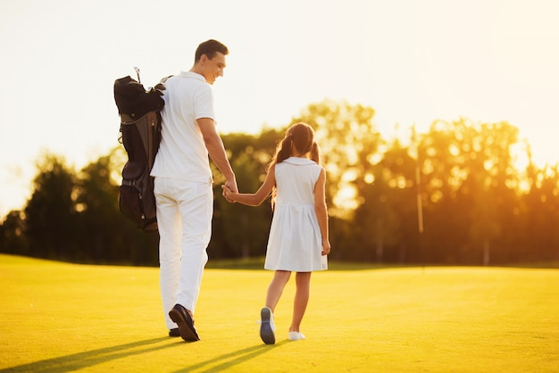 Family walks by course carries golf equipment. Premium Foto