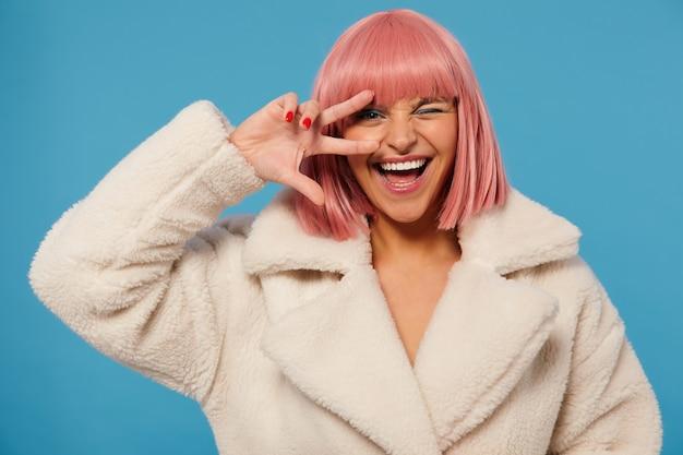 Fancy vrolijke jonge mooie dame met kort roze kapsel hand opsteken met overwinningsteken naar haar gezicht, een oog gesloten houdend Gratis Foto