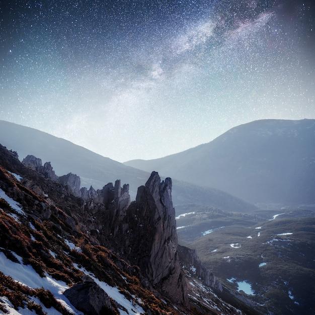 Fantastische sterrenhemel. herfst landschap en besneeuwde bergtoppen. karpaten, oekraïne europa Premium Foto