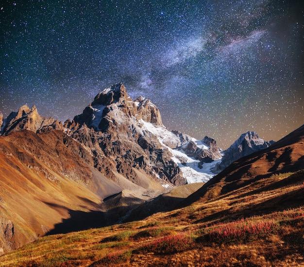 Fantastische sterrenhemel. herfst landschap en besneeuwde toppen. ma Premium Foto