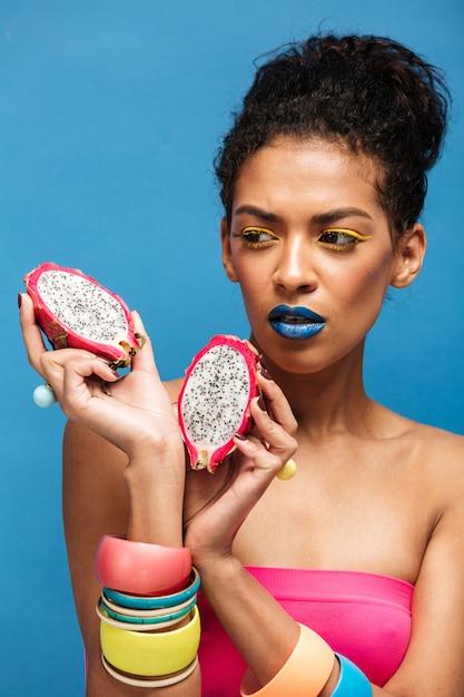 Fascinerende afro vrouw met kleurrijke cosmetica op gezicht op zoek op sappige dragon fruit in tweeën gesneden houden in beide handen geïsoleerd, over blauwe muur Gratis Foto