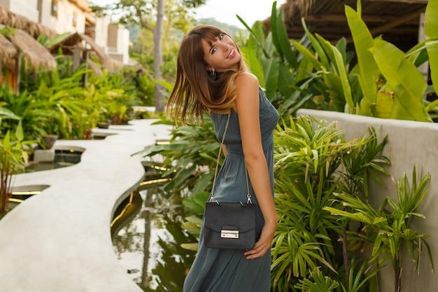 Fascinerende europese vrouw in zomerjurk wandelen in tropisch resort. groene tropische planten op achtergrond. Gratis Foto