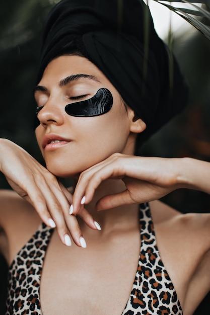 Fascinerende vrouw met ooglapjes die zich voordeed op natuur achtergrond. verbluffende jonge dame in zwarte tulband die van gezichtsbehandeling geniet. Gratis Foto