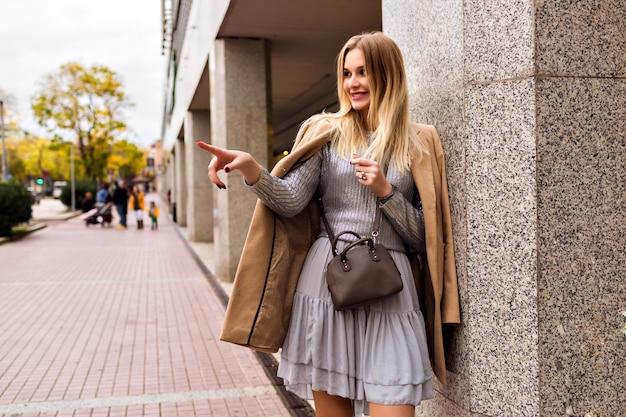 Fashion street style foto van blonde elegante vrouw, gekleed in luxe zijden jurk, trendy trui, kasjmier jas en leren tas, zachte warme kleuren, lente herfst middenseizoen stemming. Gratis Foto
