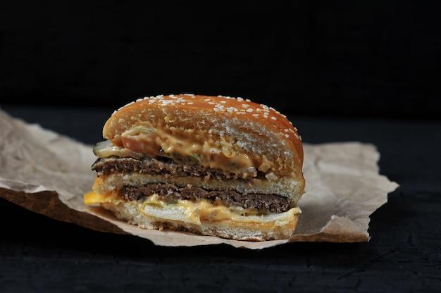 Fast food - in tweeën gesneden hamburger met kaas en rundvlees op kraft papier op zwarte houtskool achtergrond Premium Foto