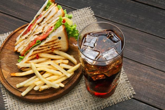 Fast-food maaltijden in sandwichbar. kip en groenten sandwich, chips en glas cola drinken met ijs op hout. Premium Foto