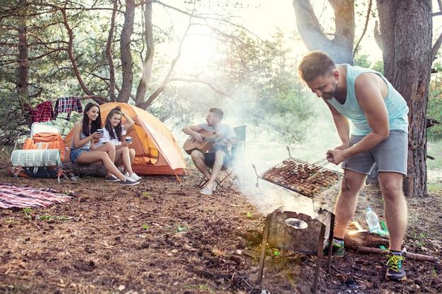 Feest, kamperen van mannen en vrouwen groep in het bos. ze ontspannen, zingen een lied en koken barbecue Gratis Foto