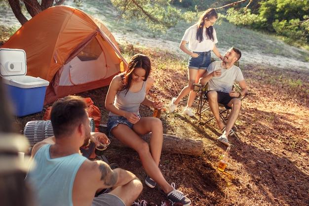 Feest, kamperen van mannen en vrouwen groep in het bos. ze ontspannen Gratis Foto