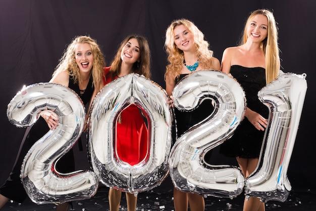 Feest, mensen en nieuwjaarsvakantieconcept - vrolijke jonge vrouwen die oudejaarsavond 2021 vieren Premium Foto