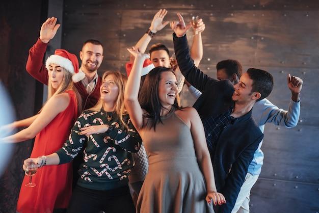 Feest met vrienden. ze houden van kerstmis. groep vrolijke jonge sterretjes en champagnefluiten die in nieuwe jaarpartij dansen en gelukkig kijken. concepten over samenhorigheid levensstijl Premium Foto