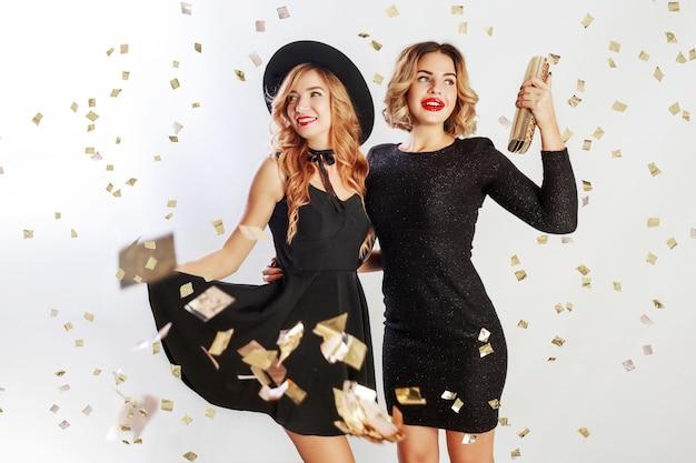Feest van twee beste vrienden, blonde vrouwen in zwarte cocktail elegante jurk poseren in studio Gratis Foto