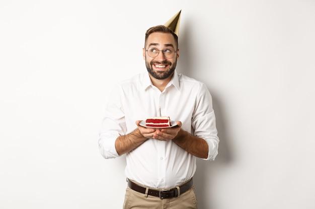 Feestdagen en feesten. gelukkig man met verjaardagsfeestje, wens maken op b-day cake en glimlachen, staan Gratis Foto
