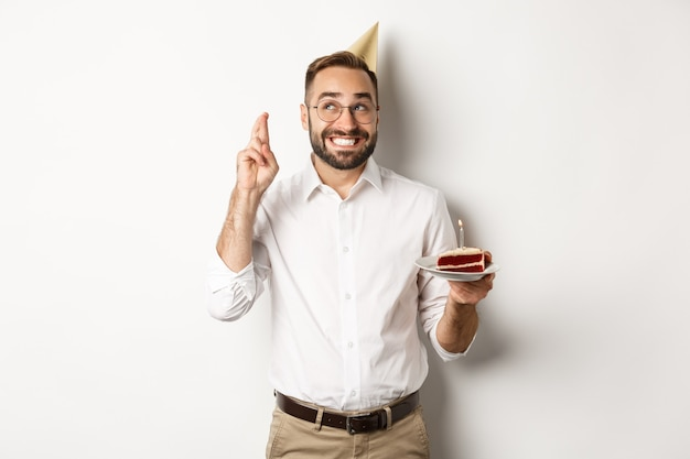 Feestdagen en feesten. gelukkig man met verjaardagsfeestje, wens maken op b-day cake en vingers voor geluk, staand Gratis Foto