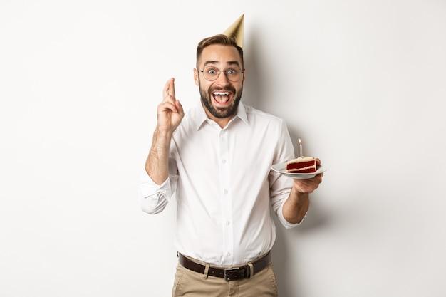 Feestdagen en feesten. opgewonden man met verjaardagsfeestje, wens maken op b-day cake en vingers voor geluk, staan Gratis Foto