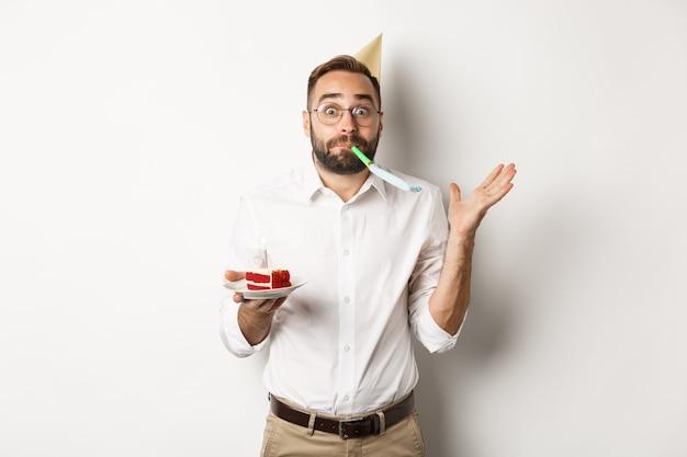 Feestdagen en feesten. vrolijke man genieten van verjaardag, partij fluit blazen en bday cake te houden Gratis Foto