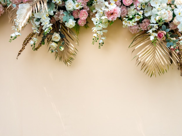 Feestdecoratie met gouden tropische palmbladeren met witte en roze rozen bloemboeket. Premium Foto