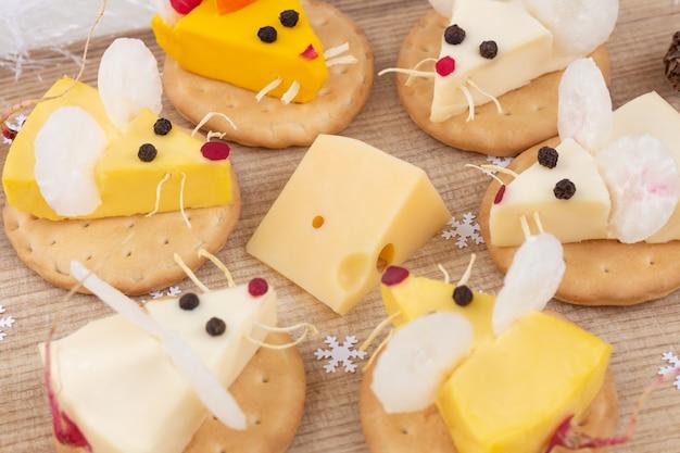 Feestelijk eten voor het nieuwe jaar - het jaar van de witte rat. muizen rond een stuk kaas. voorafje. kerststemming. Premium Foto