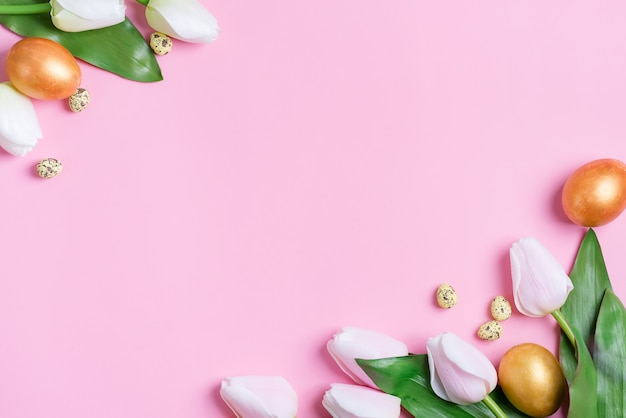 Feestelijk hoekkader van handgemaakte gouden beschilderde eieren en verse bloemen. Premium Foto