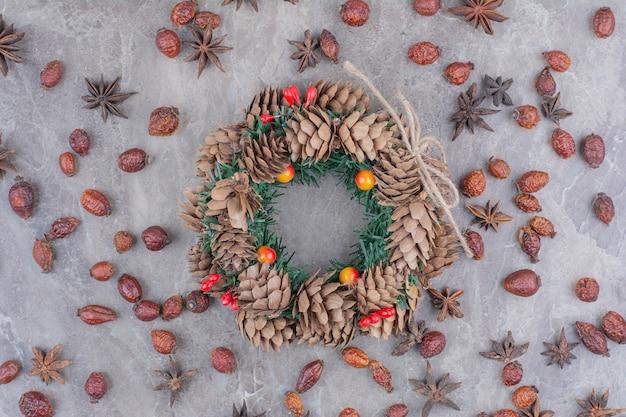 Feestelijke kerstkrans met dennenappels en steranijs op marmeren achtergrond. Gratis Foto