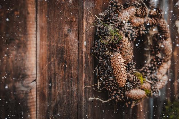 Feestelijke rustieke krans van kegels op een donkere bruine houten achtergrond. het concept van de kerstvakantie en het nieuwe jaar. Premium Foto