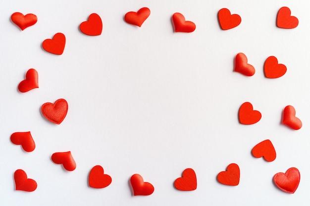 Feestelijke samenstelling van rode harten verspreid op wit voor valentijnsdag Premium Foto