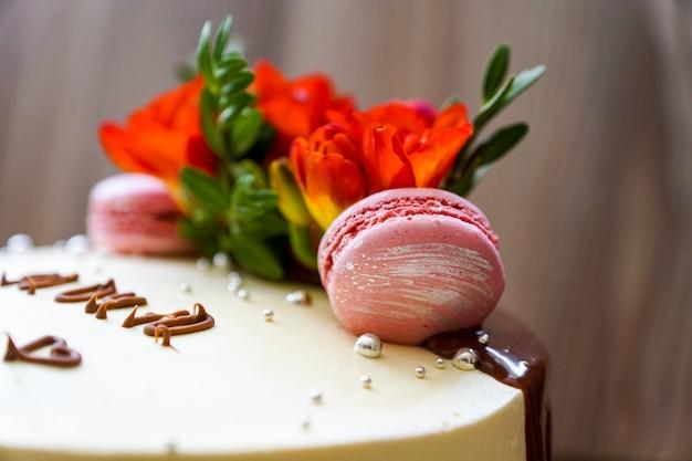 Feestelijke taartdecoratie. kokend biscuitgebak dat met verse bloemen en koekjeskoekjes wordt verfraaid Premium Foto