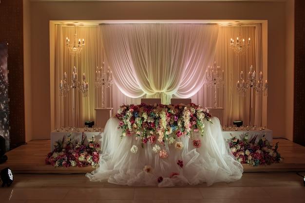 Feestelijke tafel versierd met compositie van witte, rode en roze bloemen en groen in de feestzaal. Premium Foto