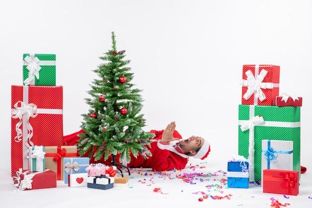 Feestelijke vakantiestemming met de jonge geschokte kerstman die achter de kerstboom ligt in de buurt van geschenken op witte achtergrond Gratis Foto