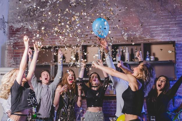 Feestelijke vrienden met confetti en ballonnen Gratis Foto