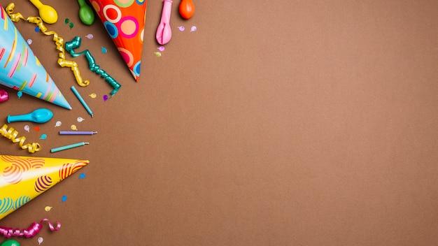 Feestmutsen; streamers; kaarsen en ballonnen met confetti op bruine achtergrond Gratis Foto