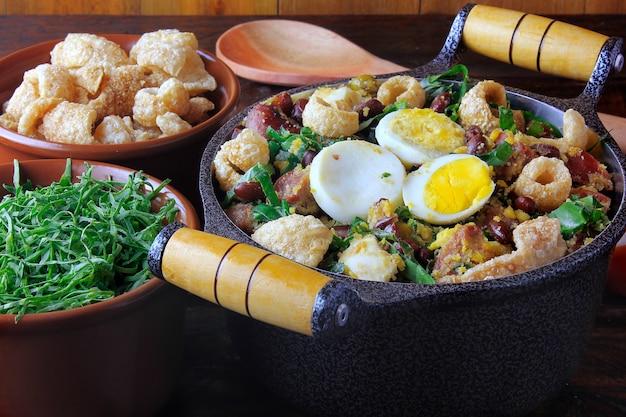 Feijao tropeiro typisch gerecht van de braziliaanse keuken, gemaakt met bonen, spek, worst, boerenkool, eieren, op rustieke houten tafel. Premium Foto