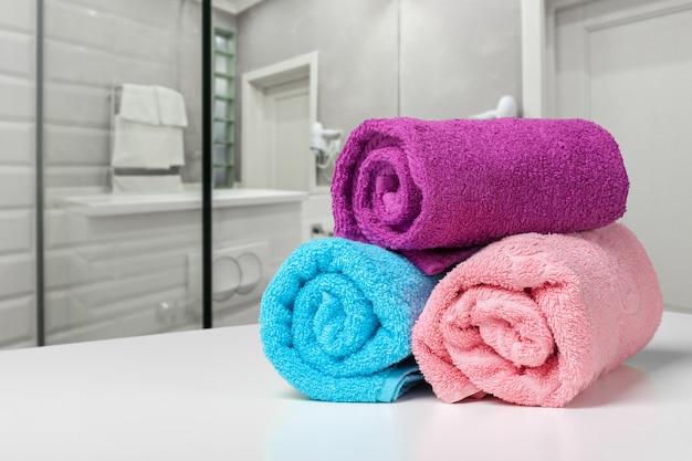 Felgekleurde handdoek op een plank in een badkamer Premium Foto