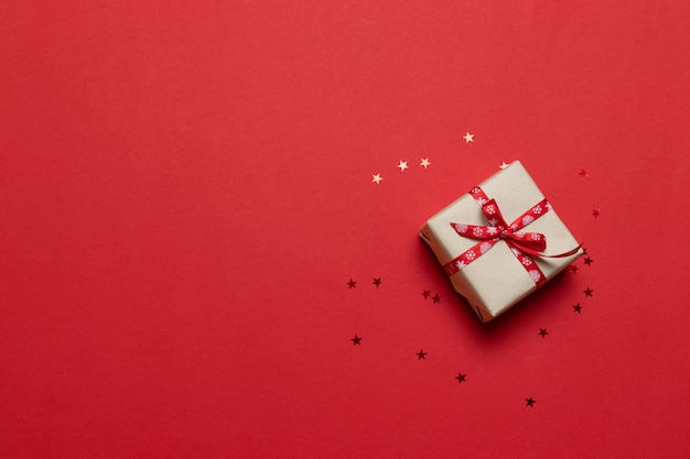 Felicitatie kaart met cadeau of huidige vak, confetti op rode tafel Premium Foto