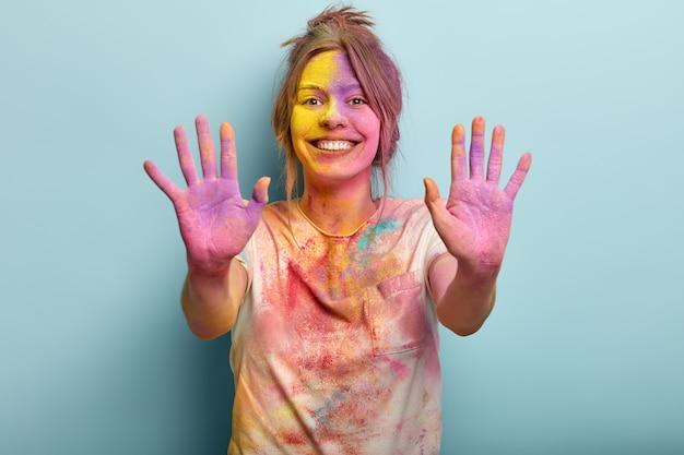 Fesitaval of holy, leuk concept. vrij vrolijke europese jonge vrouw bedekt met gekleurde verf Gratis Foto
