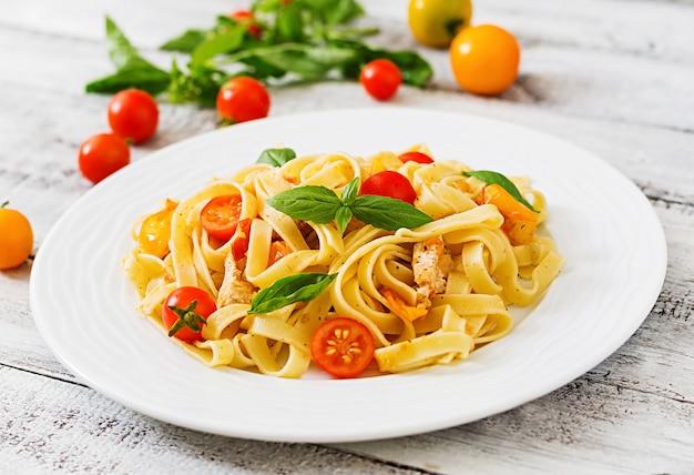 Fettuccine pasta in tomatensaus met kip, tomaten versierd met basilicum tafel Premium Foto